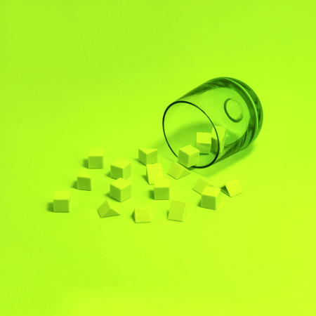 Small green cubes and pyramids scattered out of green glass on green background. Minimal monochrome image. Color game Stock Photo