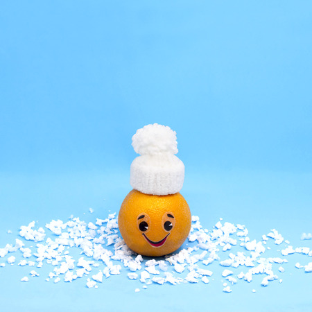 Orange in form of funny little man in white knitted hat. Creative concept: preservation of fruits and vegetables in winter. Minimal style