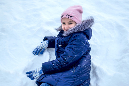 Little cute girl having fun on winter day. There is lot of snow around. Cheerful girl is sitting in snowdrift as in chair Zdjęcie Seryjne
