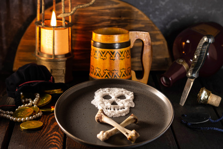 Pirate adventure story. Table of hungry pirate. Skull of salt and crossbones on plate, empty bottle, burning lantern, bag for money with gold and pearls, empty wooden mug. Selective focus 版權商用圖片