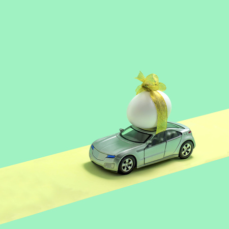 Toy car transport egg tied with ribbon. Original idea for easter decor. Creative minimal easter concept