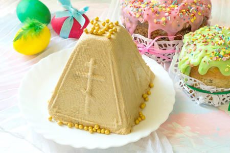 Caramel cottage cheese dessert (Paskha), Easter cakes with icing sugar and colorful painted eggs on table. Traditional Easter treats of Russia and Ukraine for Orthodox Easter. Easter symbols Zdjęcie Seryjne