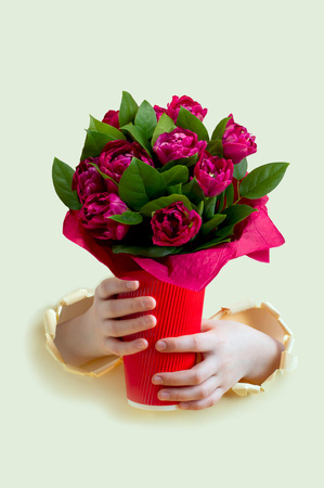 Hands hold large bouquet of tulips in red glass through torn yellow paper. Minimal holiday concept for Women's Day, Mother's Day