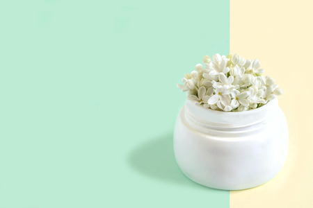 Jar with flowers of white lilac as cosmetic cream on two-color pastel background. Minimal style. Creative idea, imagination and fantasy. Concept of natural cosmetics