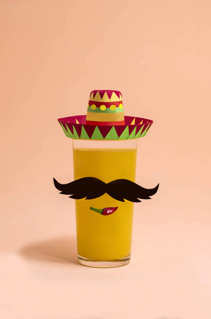 Cocktail in glass with decor for Cinco de Mayo. Paper sombrero and mustache, hot peppers for decorating drink in glass. Cinco de Mayo is federal holiday in Mexico on May 5th. Minimal holiday concept