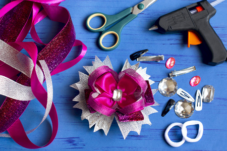 Making beautiful bows for girls hairstyle from satin and reps ribbons. Ready bow, ribbons, scissors, hairpins, scrunchy, rhinestones on blue background