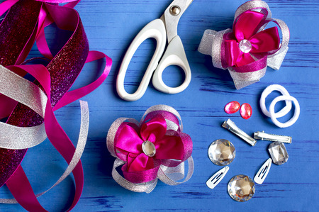 Making beautiful bows for girls hairstyle from satin and reps ribbons. Ready bows, ribbons, scissors, hairpins, scrunchy, rhinestones on blue background