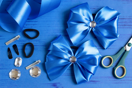 Making beautiful bow for girls hairstyle from satin and reps ribbons. Ready bow, ribbons, scissors, hairpins, scrunchy, rhinestones on blue background