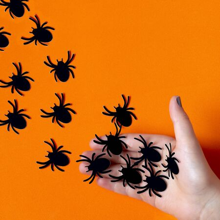 Female hand let go paper spiders. Paper art and paper craft. Festive Halloween concept Фото со стока