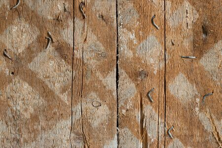 Background from old boards with traces of nailed planks. Old cracked wooden wall with nails and traces of weathering. Texture of old wooden wall