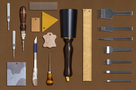 Tools for manufacture of handmade leather products. Variety of perforators, cutters, hammer and pieces of multi-colored leather. Leather handicraft and work. Flat lay, top view 스톡 콘텐츠