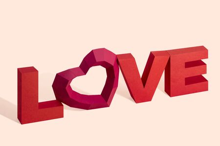 Word love made of paper with polygonal heart instead of letter O. Love lettering. Creative mock up for Valentine's Day. Paper art and craft in holiday design. Volumetric handmade paper objects