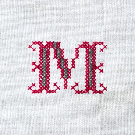 Vintage cross-stitch letter M on linen homespun fabric. Embroidered letter M close-up. Handmade art
