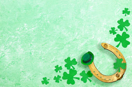 Golden horseshoe, clover shamrocks, green hat on green textured background. Festive background for St. Patrick's Day. Copy space