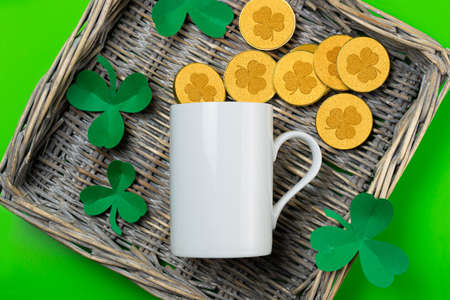 St. Patrick's Day empty white mug mockup. White coffee mug on wicker tray with coins and clover shamrocks