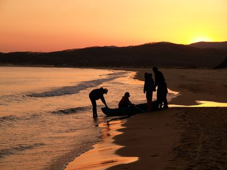 group of fisherman outward-bound against purple sunset photo