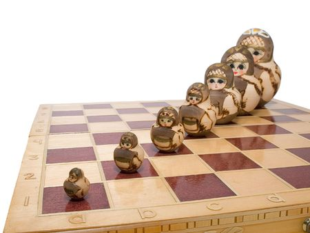 row of nested dolls on chessboard photo