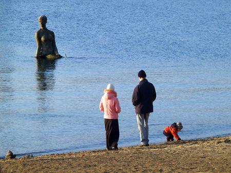 family on the beach against mermaid statue photo