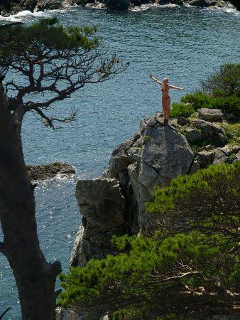 happy girl on the seaside rock photo