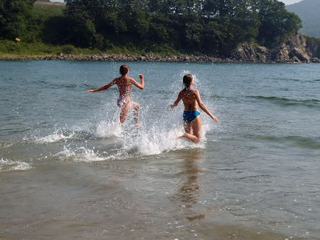 young girls running to the sea photo