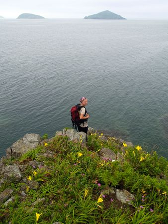 pretty girl  on the ocean rock with flower photo