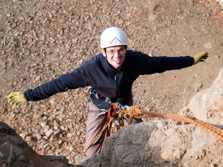 belay: climber hanging on the rock with arms wide open with happy face