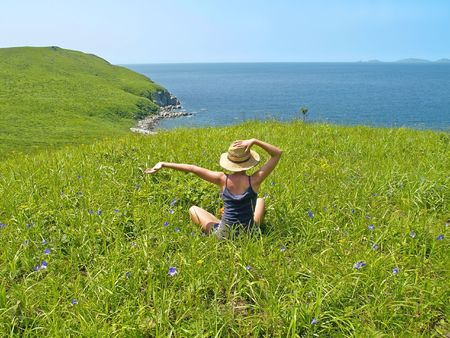 happy girl on the meadow against the sea landscape