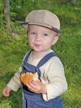 kid eating the roll in the park outdoor Stock Photo - 3588194