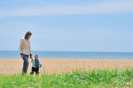family of mother and baby walking on the sea beach Stock Photo