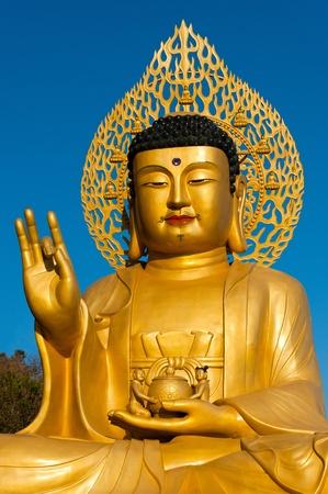 Golden Buddha statue at buddhist temple of Sanbanggulsa at Sanbangsan of Jeju island Korea photo