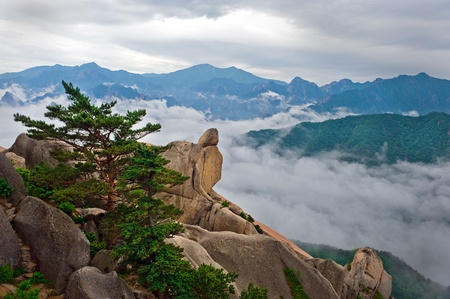 Hanging stone at the Ulsanbawi Rock against the fog seorak mountains at the Seoraksan National Park, South korea