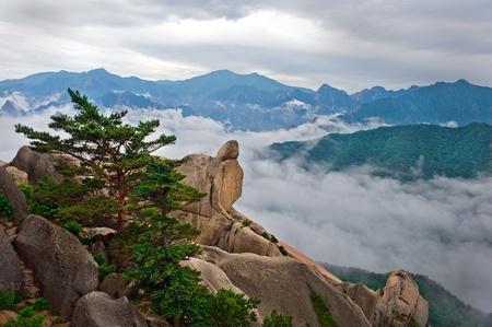 Hanging stone at the Ulsanbawi Rock against the fog seorak mountains at the Seoraksan National Park, South korea