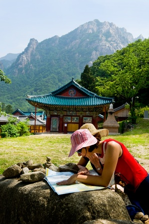 groups of travelers examining map in the Buddhist Sinheungsa Temple in Seoraksan National Park, South korea  Stock Photo