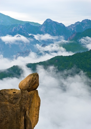 Hanging stone at the Ulsanbawi Rock against the fog seorak mountains at the Seoraksan National Park, South korea Stock Photo