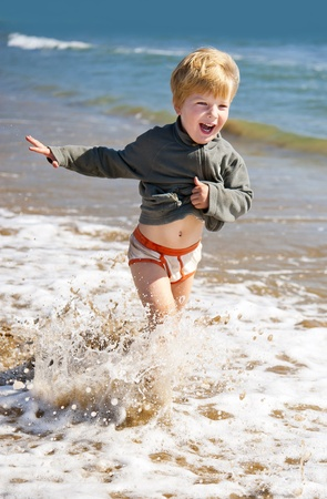 happy kid running on the sea beach  photo
