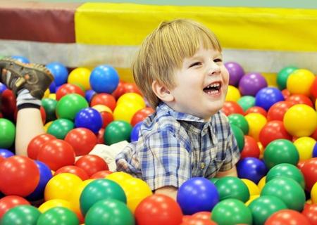 niños felices: niño feliz jugando con bolas de colores Foto de archivo