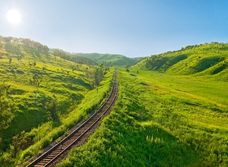 rocky road: old railway track on the morning hills landscape  Stock Photo