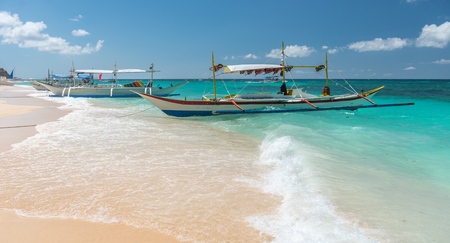 tour boats: traditional filipino asian ferry taxi tour boats on puka beach in tropical boracay island at philippines Editorial