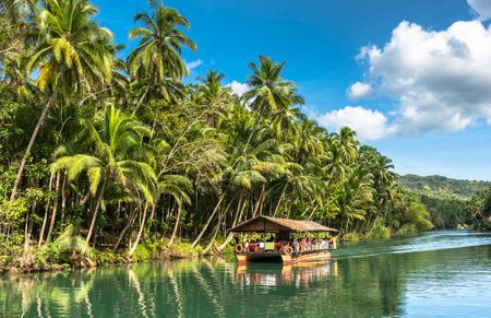 albero da frutto: barca tradizionale zattera con i turisti su un fiume verde giungla Loboc a Bohol isola di Filippine