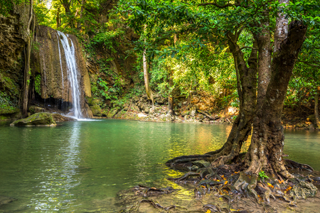 tropical forest: Jangle landscape with flowing turquoise water of third step Erawan cascade waterfall at deep tropical rain forest. Erawan Falls National Park at Kanchanaburi, Thailand Stock Photo