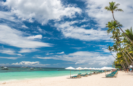 bohol: Tropical beach background from Alona Beach at Panglao Bohol island with Beach chairs on the white sand beach with cloudy blue sky and palm trees. Travel Vacation Editorial