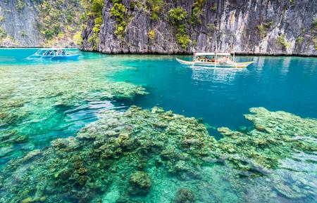 View of Kayangan Lake lagoon with tourists boat and coral reef on Coron island, Busuanga Palawan Philippines