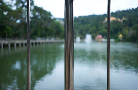 balcony: Silver metal racks near the pond and green nature.