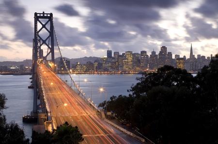 Time Exposure Bild des Verkehrs auf die Bay Bridge Treasure Island mit San Francisco in den Backgroung bei Sonnenuntergang. Standard-Bild