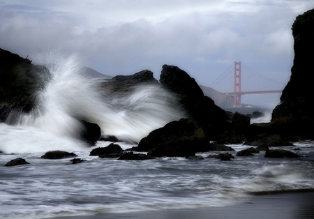 Ocean waves crash into the rocks with the Golden Gate Bridge in the background.
