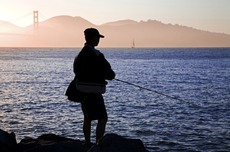 Man fishing in the San Francisco Bay with the Golden Gate Bridge in the background.