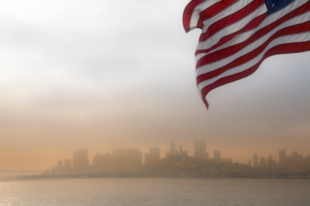 American flag fluttering with the San Francisco skyline in background at sunrise.