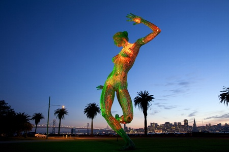 Bliss Dance 40 foot metal art sculpture by Marco Cochrane located on Treasure Island in the San Francisco Bay, Northern California, USA   Depicts a nude female in a blissful dance pose with light show at sunset