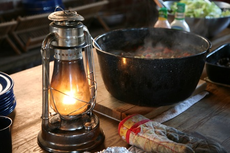 A pot of simmering beef stew beside an oil lamp
