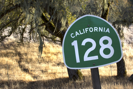 A road sign along famous California State Route 128 through Northern California wine country with oak tree and Spanish moss in the background.